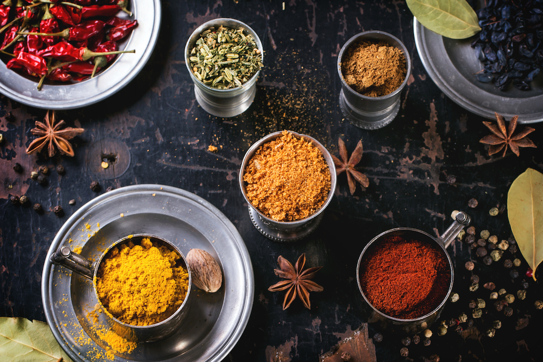 Set of spices pepper, turmeric, anise, coriander in vintage metal cups over old wooden table. Top view.